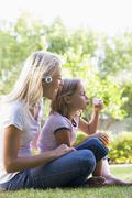 Woman and young girl outdoors blowing bubbles smiling - stock photo