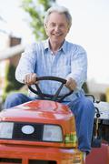 Man outdoors driving lawnmower smiling - stock photo