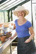 Woman in greenhouse smiling Stock Photos