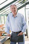 Man in greenhouse smiling - stock photo