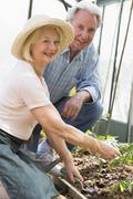 Woman in greenhouse planting seeds and man holding watering can smiling Stock Photos