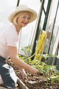 Woman in greenhouse planting seeds smiling - stock photo