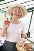Woman in greenhouse holding cherry tomatoes smiling - stock photo