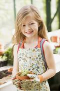 Young girl in greenhouse holding potted plant smiling Stock Photos