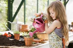 Young girl in greenhouse watering potted plant smiling - stock photo