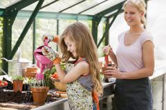 Young girl in greenhouse watering plant with woman holding pot smiling - stock photo