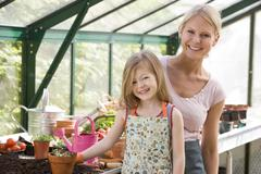 Young girl and woman in greenhouse smiling - stock photo
