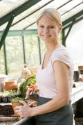 Woman in greenhouse raking soil in pot smiling - stock photo