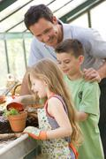 Man in greenhouse helping two young children putting soil in pot - stock photo