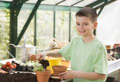 Young boy in greenhouse putting soil in pot smiling Stock Photos