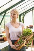 Woman in greenhouse holding basket of vegetables smiling Stock Photos