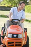 Man outdoors driving lawnmower Stock Photos