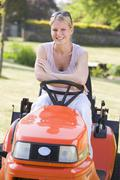 Woman outdoors with lawnmower smiling - stock photo