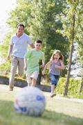Man and two young children outdoors playing soccer and having fun - stock photo