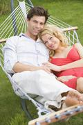Couple relaxing in hammock smiling Stock Photos
