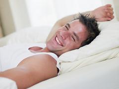 Man lying in bed laughing - stock photo