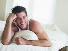 Man lying in bed smiling Stock Photos