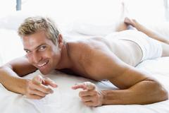 Man lying in bed pointing and smiling - stock photo
