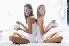 Two women sitting on bed eating cereal smiling - stock photo