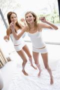 Two women jumping on bed smiling - stock photo