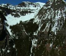 Aerial shot of snowy mountain faces on blue-sky day Stock Footage