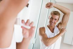 Man in bathroom applying deodorant smiling - stock photo