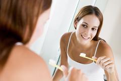 Woman in bathroom brushing teeth and smiling - stock photo