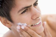 Man putting on shaving cream smiling - stock photo
