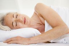 Woman lying in bed sleeping - stock photo