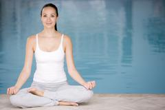 Woman sitting poolside doing yoga Stock Photos