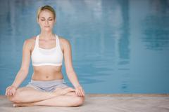 Woman sitting poolside doing yoga Stock Photos