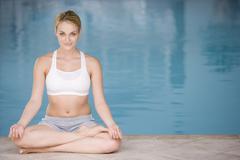Woman sitting poolside doing yoga smiling Stock Photos