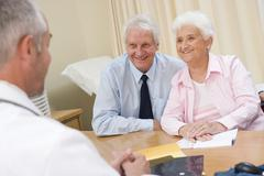 Couple in doctor's office smiling - stock photo