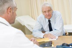 Man in doctor's office frowning - stock photo