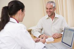 Doctor with laptop and man in doctor's office smiling - stock photo