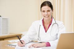 Doctor with laptop writing in doctor's office smiling - stock photo