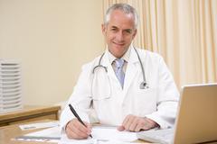 Doctor with laptop writing in doctor's office - stock photo