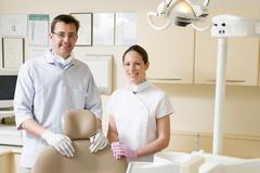 Dentist and assistant in exam room smiling Stock Photos