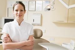 Dental assistant in exam room smiling - stock photo