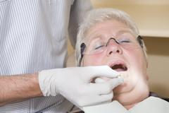 Dentist in exam room fitting dentures on woman in chair - stock photo