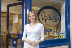 Woman standing at front entrance of optometrists smiling Stock Photos