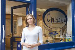 Woman standing at front entrance of optometrists - stock photo
