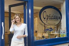 Woman standing at front entrance of optometrists smiling - stock photo