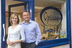 Couple standing at front entrance of optometrists smiling - stock photo