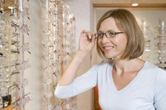 Woman trying on eyeglasses at optometrists smiling Stock Photos