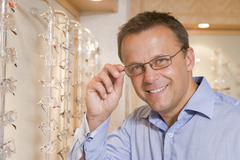 Man trying on eyeglasses at optometrists smiling - stock photo