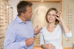 Couple trying on eyeglasses at optometrists smiling Stock Photos