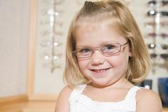 Young girl trying on eyeglasses at optometrists smiling - stock photo