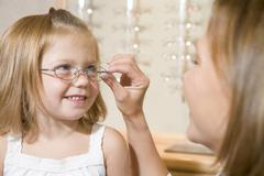 Woman trying eyeglasses on young girl at optometrists smiling Stock Photos