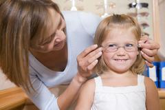 Woman trying eyeglasses on young girl at optometrists smiling - stock photo